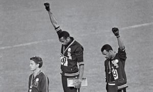 1968 Olympic Protest by USA athletes stand on podium with first in the air